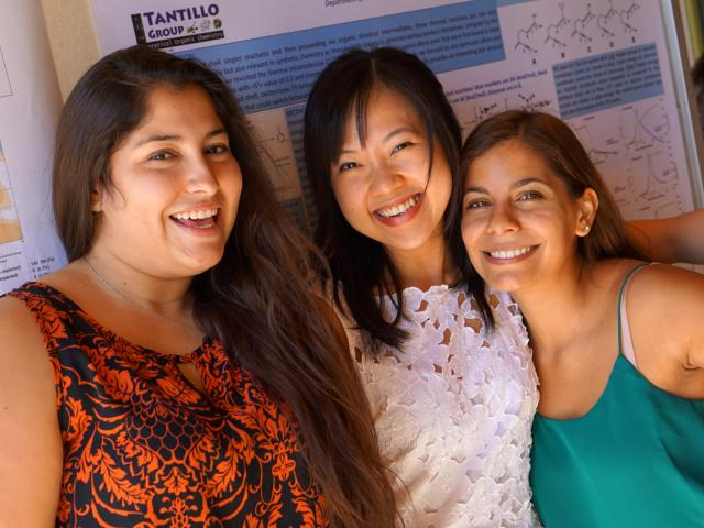 Three graduate students standing in front of a scientific poster.